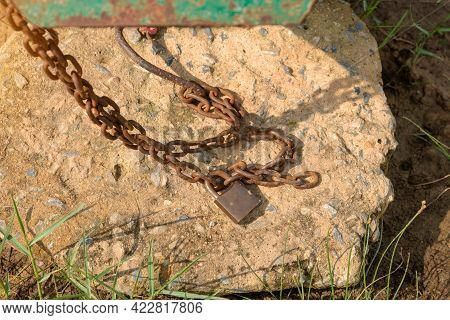 Old Lock And Rusty Chain On A Iron Boat,  Closeup Of Metal Chain On The Boat