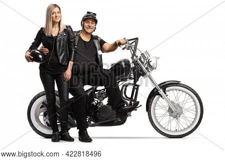 Mature biker and a young woman in leather clothes standing next to his chopper isolated on white background
