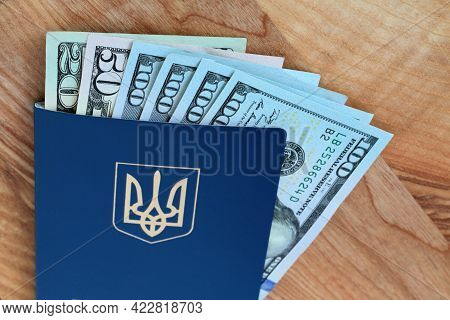 Ukrainian Passport And American Dollars Banknotes Bills On Wooden Table. Top View. Document Allowing