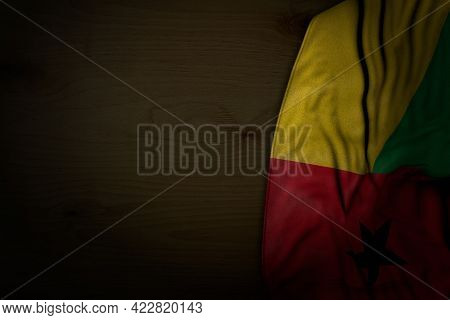 Beautiful Dark Picture Of Guinea-bissau Flag With Big Folds On Dark Wood With Empty Place For Conten