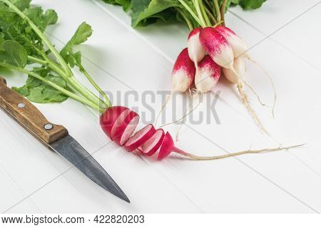 A Bunch Of Radishes, A Knife And Sliced Radishes On A White Table. A Fresh Crop Of Radishes.