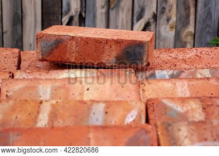 Fireclay Red Brick Lies On A Pallet Of Bricks Against Background Of Boards. Selective Focus On The B