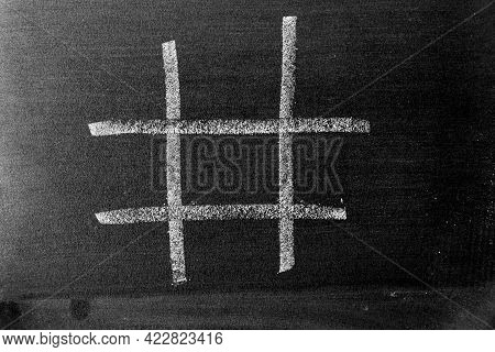 White Chalk Drawing As Hashtag Or Tic Tac Toe Blank Shape On Black Board Background