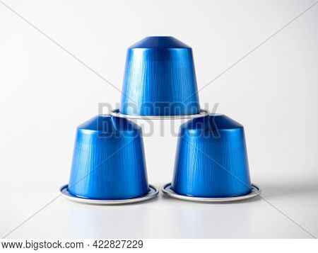 Aluminum Capsules Of Blue Color With Ground Coffee For Coffee Machines Stand On A White Background.