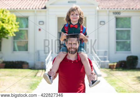 Father And Son Walking On School Park. Concept Of Friendly Family.