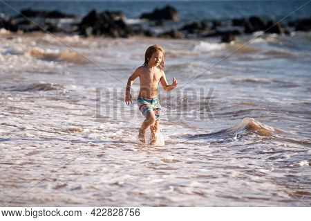 Little Child Running On The Tropical Beach. Boy Playing Sea Waves On Vacation Sea In The Summer Holi