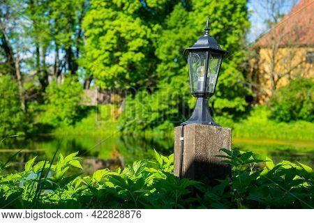 Street Wrought Metal Lantern With Green Grass In The Park