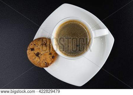 Top View. White Coffee Mug With Biscuit And Coffee On A Black Background