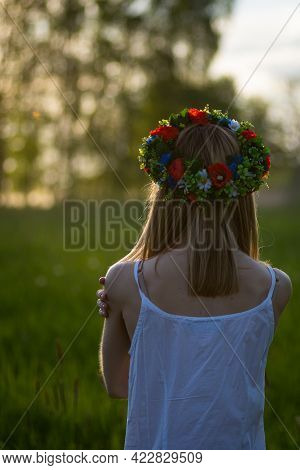 Beautiful Girl In Wreath Of Flowers In Meadow On Sunny Day. Portrait Of Young Beautiful Woman Wearin