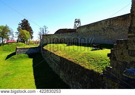 Zbarazh, Ukraine-may 11, 2021:three Medieval Cannons On Green Grass In Front Of The Defensive Wall.
