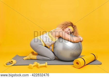 Fitness And Aerobics Concept. Tired Curly Haired Female Gymnast Leans At Fitball Dressed In Activewe