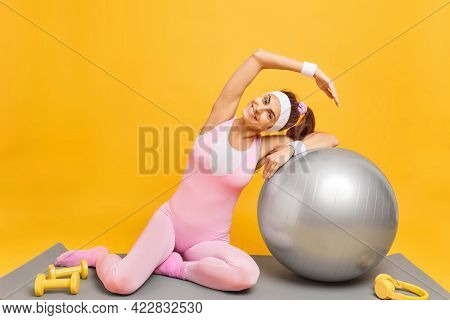 Sport Healthy Lifestyle And Exercising Concept. Positive Slim Woman Leans Aside Uses Inflated Fitbal