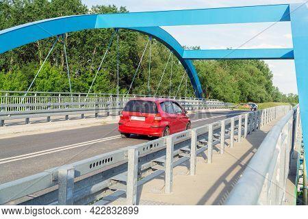 Czerwony Samochód Przejeżdża Przez Nowoczesny  Most. Poziome Zdjęcie.
