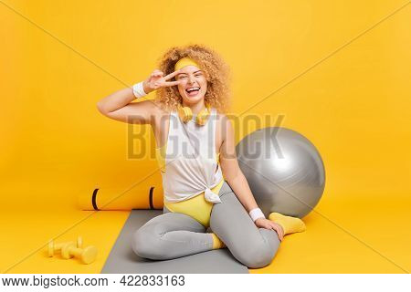 Happy Curly Woman Smiles Gladfully Makes Peace Gesture Over Eye Dressed In Activewear Poses On Fitne