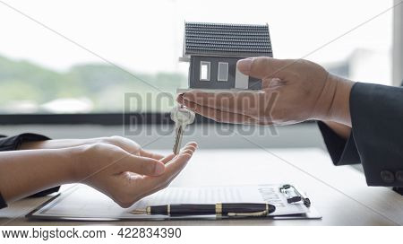 Sales manager or salesperson holds a demo house and has a home purchase contract with keys to delive