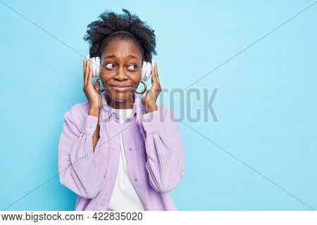 Curly Haired Young Ethnic Woman Looks Away With Pensive Expression Listens Music Via Modern Stereo H