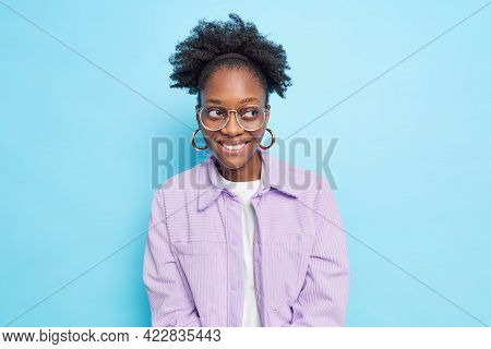 Smiling Glad Woman With Dark Skin Curly Hair Looks Away Being In Good Mood Notices Something Pleasan