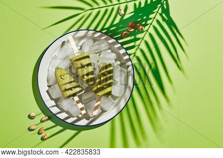 Frozen Homemade Pistachio Popsicle In Bowl Of Ice On Green Background With Palm Leaf Shadow In Harsh