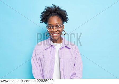 Studio Shot Of Lovely Dark Skinned Female Student Smiles Broadly Enjoys Day Off Looks Gladfully At C
