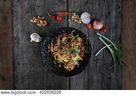 Top view of Somtam (Papaya Salad) with pork crackling isolated on rustic wooden table