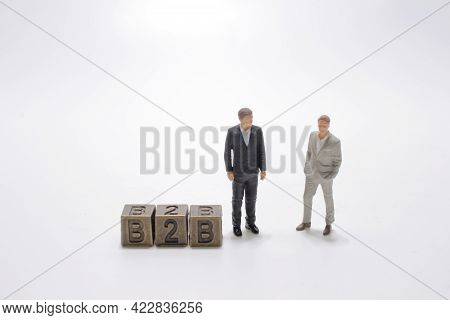 Figure Of A Man Points To An Inscription B2b On Metal Cubes