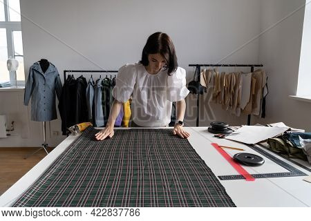 Tailor Girl Measure Cloth On Table In Dressmaking Studio. Young Designer Create Clothes In Workshop
