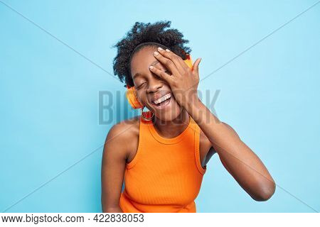 Horizontal Shot Of Glad Curly Haired Afro American Woman Makes Face Palm Smiles Positively Closes Ey