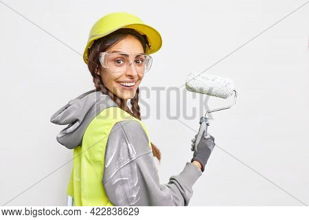 Sideways Shot Of Happy Female Construction Worker Smiles Gladfully Being Busy Painting Something Hol