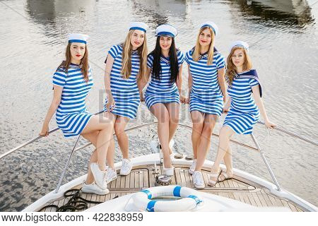 Cheerful Girlfriends In Striped Dresses And Shirts On A Yacht In The Summer. Happy Young Women Of Ca