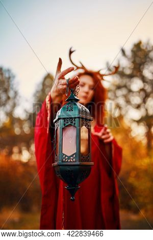 Woman In Long Red Dress With Deer Horns In Autumn Forest. The Demon Of Fairy Tales In A Red Cloak Wi