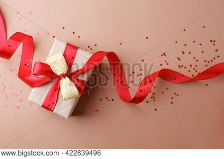 Holiday Beige Background With Gift, Red Satin Bow, Ribbon. Valentine's Day, Happy Women's Day, Mothe