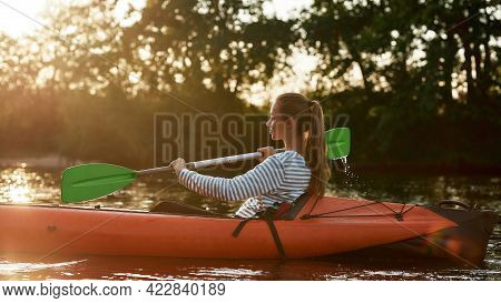 Caucasian Young Woman Holding A Paddle While Kayaking In A Lake Surrounded By Nature On A Late Summe