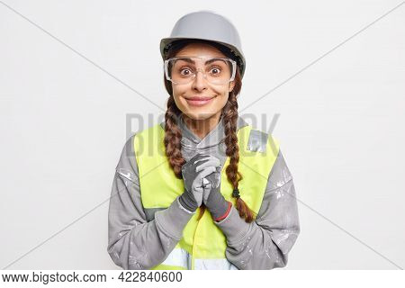 Positive Female Engineer Clasps Hands Dressed In Work Clothes Looks Happily At Camera Pleased To Hea