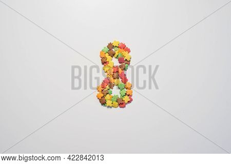 Numeral Eight From Sweet Pastry Topping In The Form Of Colorful Foliage On A White Background.