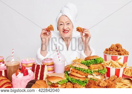 Bad Eating Habits. Happy Wrinkled Old Woman Eats Junk Food Has Obsession To Cheat Meal Wears Soft Wh