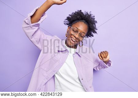 Natural Dark Skinned Curly Female Model Raises Hands Up Smiles Carefree With Closed Eyes Wears Big S