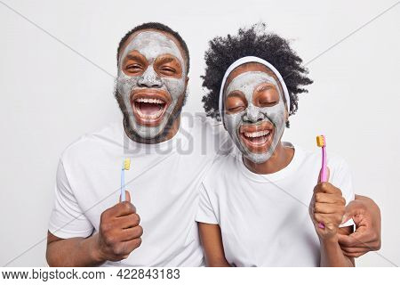 Studio Shot Of Overjoyed Dark Skinned Woman And Man Have Fun Laugh Happily Hold Toothbrushes For Cle