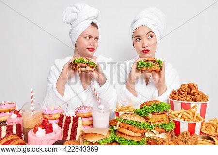 People Unhealthy Nutrition And Fast Food Concept. Thoughtful Women Eat Burgers Have Addiction To Che
