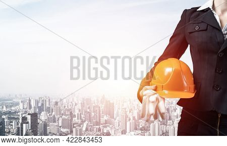 Woman Architect Holding Safety Helmet And Rubber Gloves In Hand. Female Supervisor On Background Of