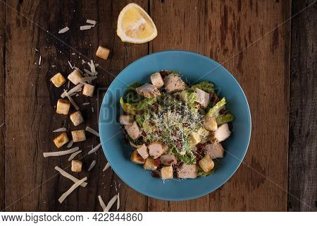 Top view of chicken Cesar salad with croutons, grated cheese and lemon isolated on wooden rustic table