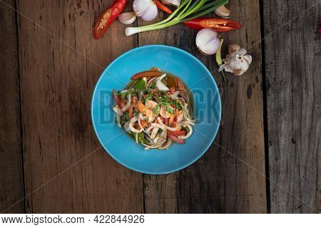 Top view of Thai spicy seafood salad with prawns, squid and Thai mussels isolated on wooden table