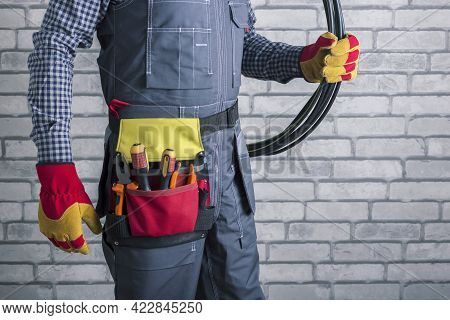 Electrician In Uniform With Wiring And Tools Near Brick Wall.