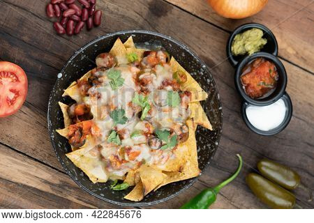 A plate of delicious corn chips nachos in cheddar cheese with beans, tomato, green chili, black olives, cilantro served with guacamole, sour cream and tomato salsa dip on the side isolated on the wood
