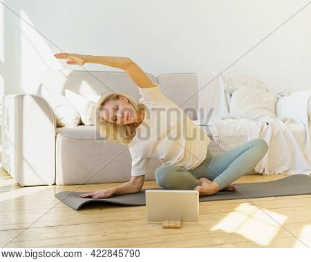 Active Retired Woman Stretching Body During Online Yoga Class At Home, Sitting In Lotus Pose On Mat