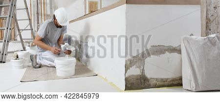 Plasterer Man At Work, Take The Mortar From The Bucket With Trowel To Plastering The Wall Of Interio