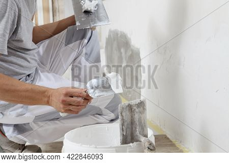 Hands Man Plasterer Construction Worker At Work Closeup, Takes Plaster From Bucket And Puts It On Tr