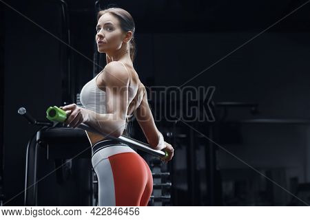 Athletic Fitness Woman At Workout In Gym With Body Bar Stretching Muscles. Fitness And Sport Concept