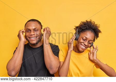 Positive Carefree Dark Skinned Woman And Man Listen Music Via Wireless Headphones Smile Happily Have