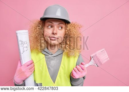 Thoughtful Hesitant Female Builder Contractor Looks Away With Clueless Expression Holds Painting Bru