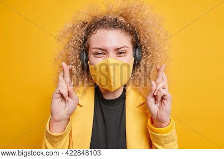 Happy Curly Haired Woman Wears Protective Face Mask Against Coronavirus Wishes Good Luck Keeps Finge
